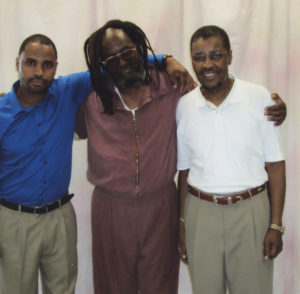 After decades on death row, where prisoners and visitors are separated by glass, Mumia had to fight another year and a half to win contact visits with his oldest son, Jamal, shown here on the left. Mumia's oldest brother, Keith Cook, is on the right.