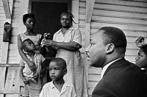 """After passage of the Civil Rights Act, Dr. Martin Luther King Jr. focused on economic racism. He learned how people – urban and rural – cope with deep poverty by visiting them, often staying as a guest in their home for a time. Here he visits a family in Greenwood, Miss., in July 1964. When he died, he was finalizing plans for the Poor People's Campaign. But that work is far from finished. The Black poverty rate in 2011 was almost as high as in 1969, the year after King was assassinated. Dr. King said, """"America is going to hell if we don't use her vast resources to end poverty and make it possible for all of God's children to have the basic necessities of life."""" – Photo: Jim Bourdier, AP"""