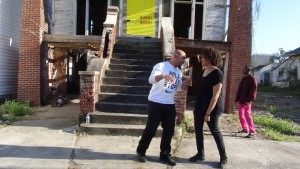 "Poet Frederick ""Hollywood"" Delahoussaye, who had been relocated to the Bay Area after Katrina and is now teaching in New Orleans, with dancer Keisha McKay and the second line honored the loss to the community these empty homes represent. – Photo: Wanda Sabir"