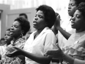 Young women sing freedom songs in a Selma church on July 8, 1964. – Photo: © Matt Herron, Take Stock Photos