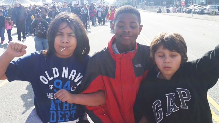 During the annual Martin Luther King Day march that draws thousands from around the Bay Area to San Francisco, Deecolonize Academy students Kimo Umu, Ty'Ray Taylor and Tibucio Gray-Garcia Robles locked arms the way Dr. King used to do. – Photo: Poor News Network