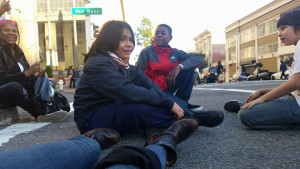 """After seeing the movie """"Selma,"""" the Deecolonize students staged a die-in outside the theater at the intersection of Van Ness and O'Farrell. Kimo Umu, Ty'Ray Taylor and Tibucio Gray-Garcia Robles showed that children can muster the courage to demonstrate and even stop traffic for justice. – Photo: Poor News Network"""