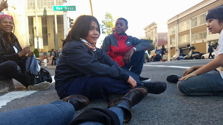 "After seeing the movie ""Selma,"" the Deecolonize students staged a die-in outside the theater at the intersection of Van Ness and O'Farrell. Kimo Umu, Ty'Ray Taylor and Tibucio Gray-Garcia Robles showed that children can muster the courage to demonstrate and even stop traffic for justice. – Photo: Poor News Network"