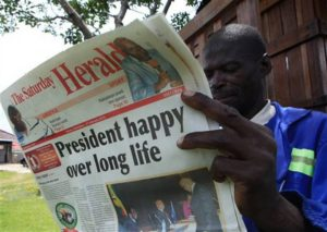 A Zimbabwean in Harare reads the state-owned Herald on President Mugabe's 91st birthday, Feb. 21, 2015, also the anniversary of the assassination of another pan-Africanist, El Hajj Malik El-Shabazz  - Malcolm X – who was gunned down at 39. He would have been 89 today. – Photo: Tsvangirayi Mukwazhi, AP