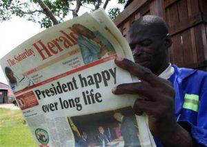 Zimbabwe-man-reads-Herald-on-Mugabes-91st-birthday-022115-by-Tsvangirayi-Mukwazhi-AP-300x213, At 91, President Mugabe leads Zimbabwe, SADC and African Union – with vigor, World News & Views