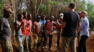 "In the 60 Minutes story ""The Ebola Hot Zone,"" broadcast Nov. 9, 2014, Lara Logan watches as American virologist Joseph Fair instructs Liberian gravediggers at a graveyard adjacent to an Ebola treatment unit. No African voice is heard in the 15-minute segment except that of the African American doctor who heads the clinic and speaks a few words. – Photo: 60 Minutes screenshot"