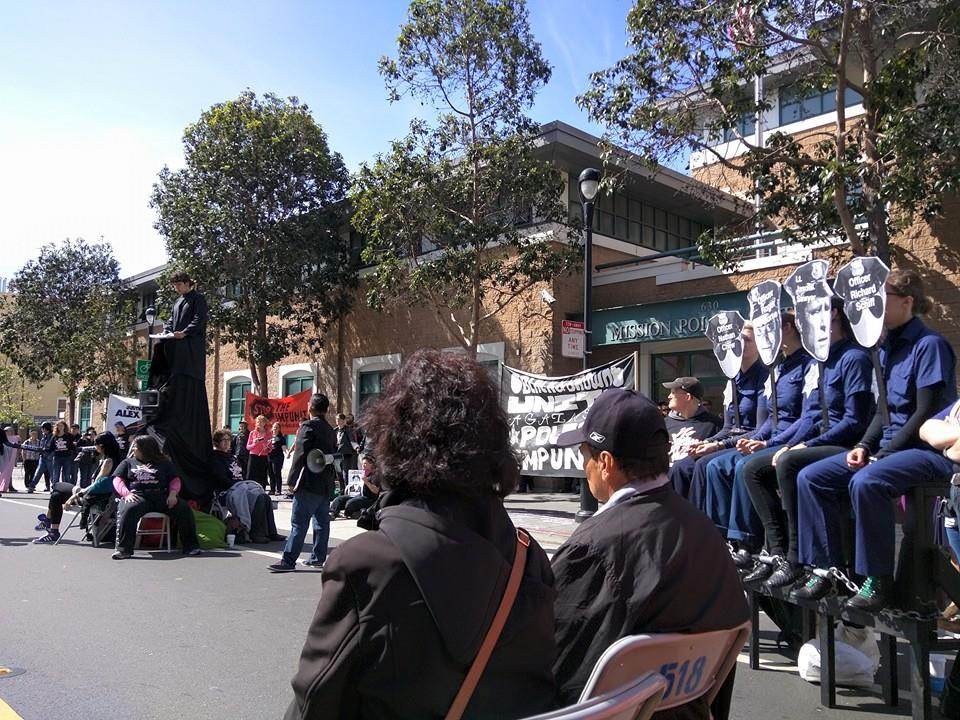 Most of the complex panoply on the street in front of the Mission Police Station is shown here, with the mock trial of the four officers involved in Alex's murder – Lt. Jason Sawyer and Officers Roger Morse, Richard Schiff and Nathan Chew – after DA Gascón exonerated them, having initially promised their parents he would help. – Photo: Adriana Camarena