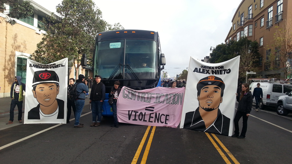 Serving as a means of blocking off the street in front of the Mission Police Station, an eBay bus had been stopped by the protesters near the beginning of the 7 a.m. protest and was held there for over four hours. The Mission is in mourning and enraged about the murder of Alex Nieto a year ago and the murder of Amilcar Pérez-López just a month ago, on Feb. 26, 2015. – Photo: Stop Police Impunity