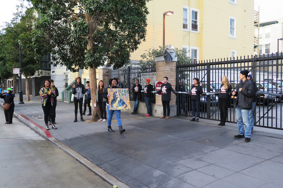 While some protesters locked themselves down to structures they'd built and placed in the street, others blocked the driveway to the Mission Police Station parking lot. During the four-and-a-quarter-hour protest, police could not drive in and out, but they could enter and exit the station on foot because, unlike a similar police station shutdown in Oakland recently, the protesters did not lock down the station entrances. – Photo: Jesús Barraza