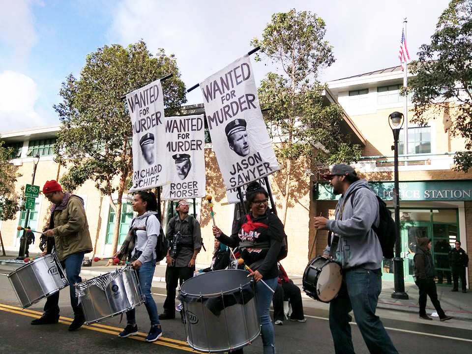 """Who says protesters can't have fun. Black-Brown unity is on display as Black protesters drum while carrying """"wanted"""" banners strapped to their backs. – Photo: Adriana Camarena"""