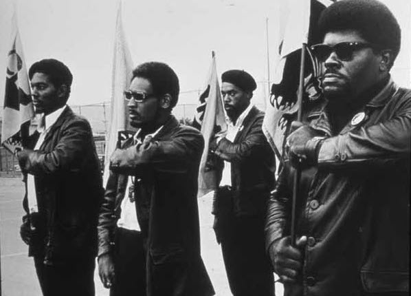Black Panthers drill with Big Man, one of the founders of the party, at a Free Huey rally in Bobby Hutton (DeFremery) Park in July 1968. The issues he addresses here are much the same as the issues the Panthers addressed so effectively then that they remain a model for us today. – Photo: Pirkle Jones