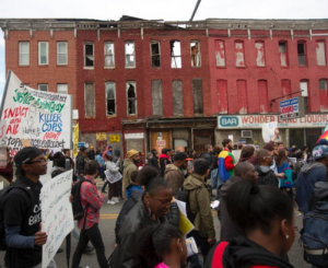 Marchers pass buildings literally falling down in an oppressed neighborhood whose people too have been abandoned and are locked out of the economy.