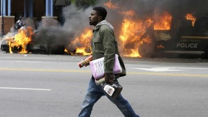A young man walking past burning police vehicles and carrying items he may have liberated from a store exemplifies the contempt for both public officials and private corporations that springs naturally from intense oppression.