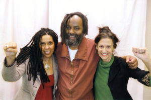 Johanna Fernandez (left) and Heidi Boghosian visit Mumia on Feb. 7, 2012, in the exciting days after he was finally released from 30 years in solitary confinement. Finally, he could have visitors he could touch – no glass separating them – and he was allowed to have his picture taken for the first time since 1996. He had recently been transferred to SCI Mahanoy, the prison where medical neglect has come close to killing him.