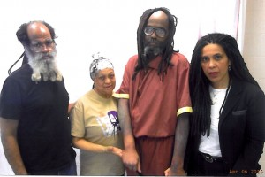 For this photo, taken April 6, 2015, in the infirmary at SCI Mahanoy, Mumia was embarrassed to be shown in a wheelchair but could barely stand. Visiting him are Abdul Jon, Pam Africa and Johanna. He is still using a manual wheelchair, which requires all of his meager strength to travel from the infirmary to the visiting room.