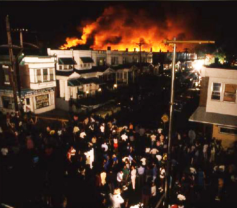 A crowd gathers to watch the conflagration, which had consumed the entire 6200 block of Osage Avenue in a Black middle-class neighborhood by the time the firefighters were told to aim their hoses at it.