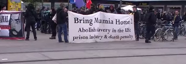 Supporters of Mumia Abu-Jamal marched to stop his execution by medical neglect in Berlin in April 2015. – Video: Anton Mestin