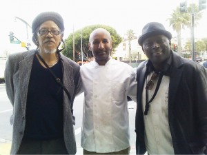 Outside his restaurant, Radio Africa and Kitchen, at Third and Oakdale, is the main man, Chef Eskender Aseged, flanked by musicians Sam Peoples and Charles Under. – Photo: Rochelle Metcalfe