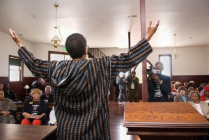 Rev. Mutima Imani of the East Bay Church of Religious Science in Oakland leads a ceremony inside First Baptist Church in Allensworth for other visitors. Entering Allensworth buildings enables Black people to commune with this great landmark of California Black History.
