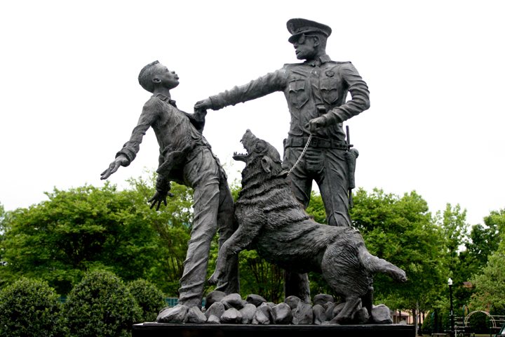 Birmingham Police Chief Bull Connor turned vicious police dogs and water hoses on children when their Children's Crusade in May 1963 attempted for several days to march to City Hall to meet with the mayor. In September 1963, the brutal suppression culminated in the murder of the four little girls at the 16th Street Baptist Church. Today, the events are memorialized in lifelike statues mounted in Birmingham's Kelly Ingram Park. – Photo: Shino, Flickr