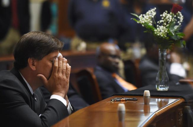 In the South Carolina Senate chambers on Thursday, Sen. Clementa Pinckney's place is draped in memorial. In the neighboring seat, Sen. Vincent Sheheen weeps. – Photo: AP