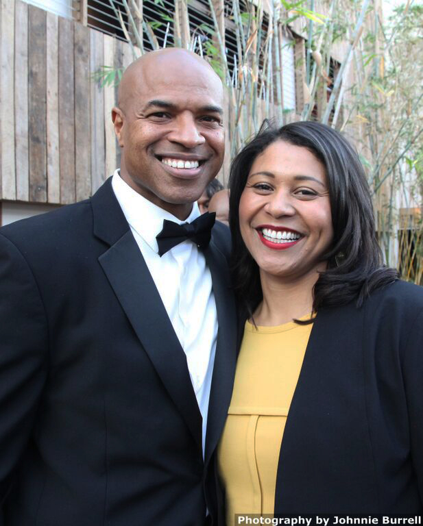 """Charleston Pierce, who plays Charlie Walker in """"America Is Still the Place,"""" and San Francisco Board of Supervisors President London Breed pose on the Red Carpet on opening night, all smiles in anticipation of a great show. – Photo: Johnnie Burrell"""