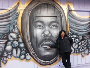 Denika Chatman, mother of Kenneth Harding Jr., stands proudly beside a beautiful mural of Kenny on the Bishop Building, just a few steps from where he was murdered. The mural was dedicated on Jan. 16, 2015, to the joy of those who have fought for justice for him, but a short time later, without notice, it was painted over.