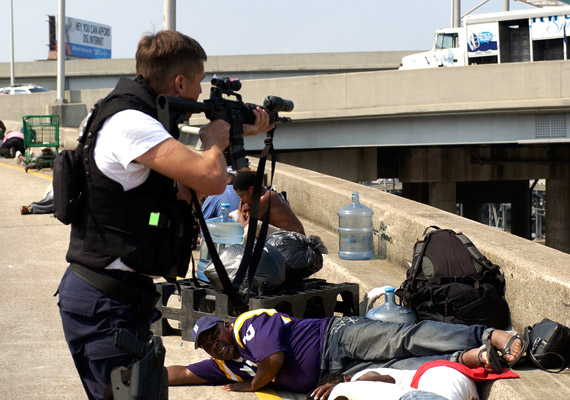After Katrina, police were told they could shoot looters. New Orleans Police Lt. Dwayne Scheuermann aims his gun on the Claiborne Overpass on Sept. 1, 2005, two days after the storm, while the people around him on the bridge are desperate for help. – Photo: Alex Brandon, New Orleans Times-Picayune