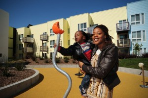 Resident Jasmine Hudson and her son are smiling in this promotional photo taken at the grand opening of the big Bridge Housing development called Ironhorse at Central Station in Oakland. But many other low-income renters are excluded by the high minimum income requirements. All but 20 of the 99 apartments are for residents making $18,000-$50,000 annually. – Photo: Julio Cesar Martinez