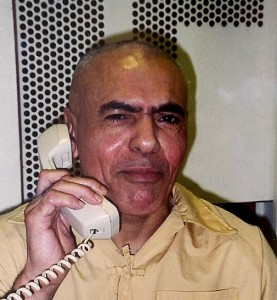 """Hugo """"Yogi"""" Pinell talks with a visitor in 2001 on the phone at Pelican Bay State Prison – thick glass in a concrete wall dividing them. Through his decades in Pelican Bay, he was never able to touch a visitor or any friendly person."""