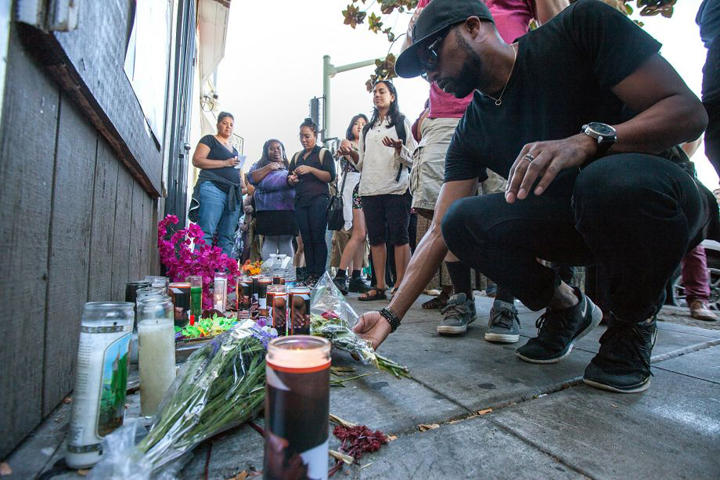 David Craig of Oakland lays flowers at 27th Street and Martin Luther King Jr. Way, Friday, Aug. 14, in Oakland during a vigil for Nathaniel Wilks, who was shot and killed by Oakland police. – Photo: Santiago Mejia, Special to SF Chronicle