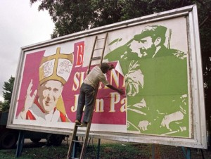 As Cuba prepares for the papal visit, a worker replaces a message featuring Fidel Castro with another welcoming Pope Francis on a billboard. – Photo: Reuters