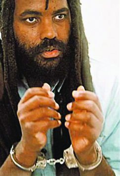 Mumia-in-handcuffs-looking-up-color, Mumia Abu-Jamal's eighth book: 'Writing on the Wall', Culture Currents