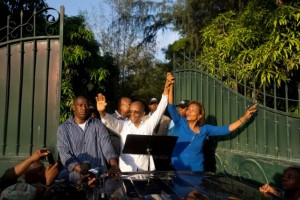 Former President Dr. Jean-Bertrand Aristide and Lavalas presidential candidate Dr. Maryse Narcisse, standing in the bed of a pickup truck, greet a huge crowd waiting at the gates of his home. – Photo: Dieu Nalio Chery, AP