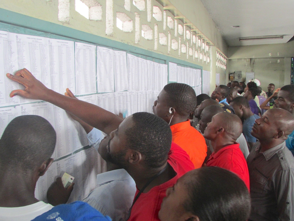 In the upscale neighborhood of Petionville, at the polling place across the street from the plush new Hotel Kinam where President Michel Martelly and presidential candidate Jude Celestin had cast their votes earlier in the day, voters searched for their ID numbers on the wall prior to voting. – Photo: John Carroll