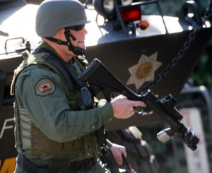 "A Sonoma County sheriff's deputy, part of a SWAT team, stands in front of the Sheriff's Department's huge tank, or ""armed personnel carrier."" Sonoma County, in California's wealthy wine country, is heavily militarized. – Photo: Santa Rosa Press Democrat"