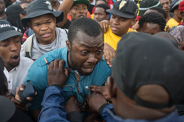 Students from the University of Johannesburg clash with campus security officers, as they attempt to enter inside the university, on October 22, 2015, in Johannesburg, during a protest against university fee hikes. University activism has been increasing this year as students vent their anger over the limited racial transformation in education since racist white-minority rule ended with Nelson Mandela's election in 1994. Many students says higher fees -- which could rise by 10 percent a year -- will further prevent poorer black youths gaining university education. AFP PHOTO / MUJAHID SAFODIEN        (Photo credit should read MUJAHID SAFODIEN/AFP/Getty Images)