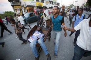 Protesters cart the body of a demonstrator who was killed by a gunshot in during a protest march against official preliminary election results, in Port-au-Prince, Haiti, on Friday, Nov. 20. According to those official results, Martelly-backed candidate Jovenel Moise and Jude Celestin finished first and second to win spots in the Dec. 27 runoff. – Photo: AP