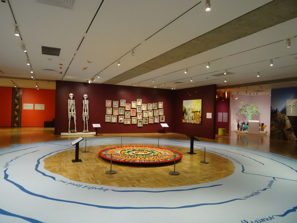 "In this view of the Oakland Museum gallery featuring the Dia de los Muertos exhibit, the story tree in the back right corner has recorded stories by high school youth recalling their ancestors and talking about their ancestry, along with headphones for visitors to listen. ""I listened to all their stories,"" Wanda says. – Photo: Wanda Sabir"