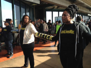 On Black Friday last year, Nov. 28, 2014, Alicia Garza, right, and other Black Lives Matter activists shut down BART trains carrying shoppers to and from San Francisco for three hours by chaining themselves simultaneously to eastbound and westbound trains stopping at the West Oakland BART Station. The Black Friday 14, as the arrested protesters are called, still face criminal charges and a $75,000 fine. Their next court date is Dec. 10. – Photo: Julia Carrie Wong, Special to SF Examiner