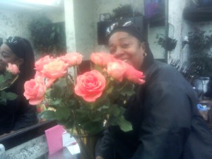 Linda Jamerson, owner of Scorpion's Hair Salon on Third Street, smells her beautiful roses, a gift for her birthday. – Photo: Rochelle Metcalfe