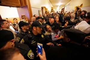 The hundreds who came to protest the murder of Mario Woods at the Police Commission hearing Dec. 9 packed the hearing room and an overflow room, the rest forced to crowd the hallway outside. Their chanting could be heard during the hearing. Rage at gentrification and police murders has forged strong solidarity between San Francisco's Black and Brown communities. – Photo: Marcio Jose Sanchez, AP NYT