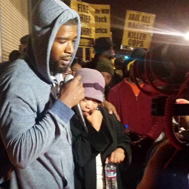 """Mario Woods' cousin Jeff Stewart consoles Mario's mother as she weeps in his arms over her murdered son. """"They're going to paint my child out to be a monster, and he wasn't a monster,"""" she said. """"He would give you the shirt off his back."""""""
