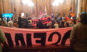 "Protesters took over the Board of Supervisors Budget Committee Dec. 2. After nearly two hours of dull budget wrangling, when the clerk announced the jail agenda items, a whistle interrupted him and out came the banners: ""NO SF JAIL"" and ""DON'T LOCK UP OUR BUDGET."" At that point, the meeting descended into a festival-like atmosphere of shouting, stomping and chanting that went on for over an hour. – Photo: Adam Brinklow"