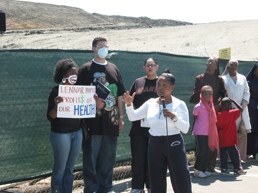 Ahimsa Sumchai, M.D., expert on the radiological history of the Shipyard and on the effects of toxic exposure, speaks at an Aug. 25, 2007, rally at Muhammad University, a school located next to the Shipyard fence, where students were bombarded with toxic dust for years. Behind the protesters is the moonscape Lennar created as its giant earthmovers removed 35 feet of Hunters Point Hill. – Photo: Chris Brizzard