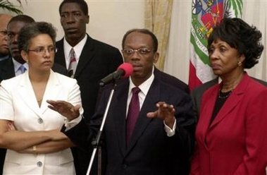 Congresswoman Maxine Waters is loved and heralded in Haiti for her fearless advocacy for the people. Here, on Feb. 21, 2004, she stands with then President Jean Bertrand Aristide and his wife, Mildred Aristide, at a press conference in the presidential palace, just eight days before the coup that forced the Aristides into exile. – Photo: Pablo Aneli, AP