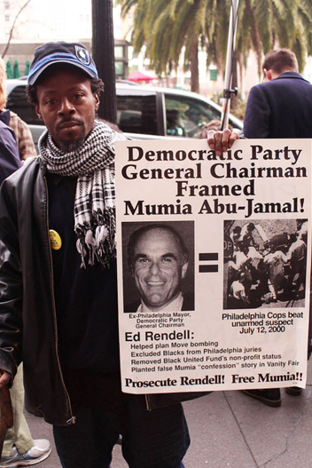 Fearless advocate for justice Jabari Shaw displays a poster showing how deeply involved powerful politicians are in the decades of persecution of Mumia Abu-Jamal. – Photo: Anka Karewicz