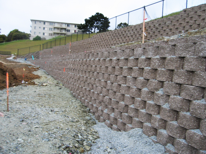 A series of retaining walls – apartheid walls – was built by Lennar to hold the hill where they cut it down to 35 feet below the Hunters Point hilltop, densely populated with Black families, apparently to separate and protect the upscale neighborhood they envisioned from Black children who might have the audacity to visit. – Photo: Dr. Willie Ratcliff