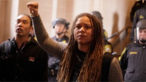 In the face of riot cops at Mayor Ed Lee's inauguration Jan. 8, Melissa Crosby leads protesters in the Assata Shakur chant. – Photo: Noé Serfaty