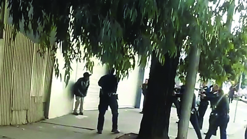 A frame from the video seen worldwide shows police officers forming the firing squad that executed Mario Woods.